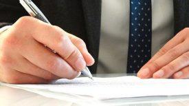 hands signing divorce forms
